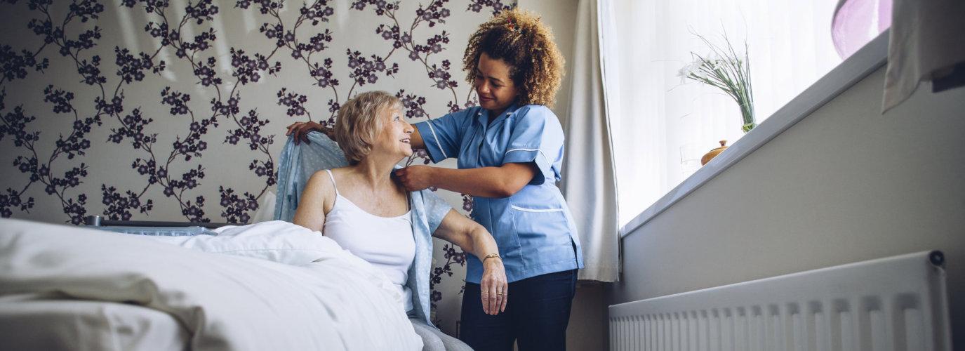 caregiver helping senior get dressed
